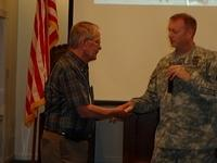 COL Stuart McRae, the Installation Commander at Fort Rucker passes Ross McKimmey a coin